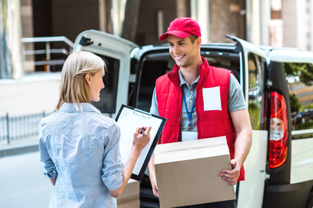 delivers: Colorful picture of courier delivers package for woman. Woman is signing the dokument and smiling. Stock Photo