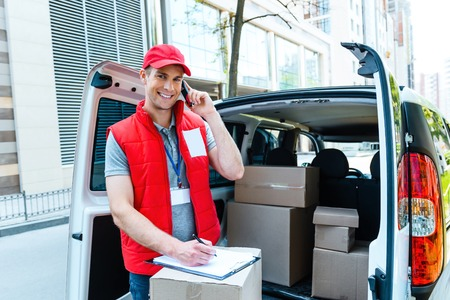 delivers: Colorful picture of courier delivers package. Courier talking on the phone, looking at camera and smiling.