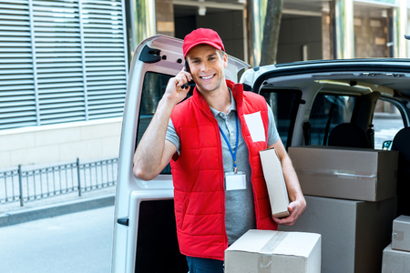 courier: Colorful picture of courier delivers package. Courier talking on the phone, looking at camera and smiling.