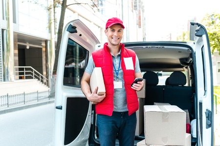 Colorful picture of courier delivers package. Courier holding the box and phone, he smiling. Foto de archivo