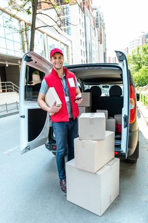 Colorful picture of courier delivers package. Courier holding the box and phone, he smiling. Stok Fotoğraf