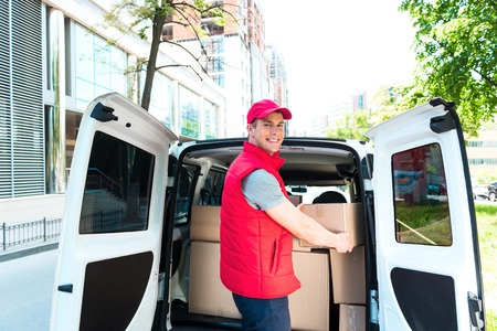 Colorful picture of courier delivers package. Courier picking up the parcal from the car and smiling. Stock Photo