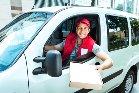 delivers: Colorful picture of courier delivers package. Man is riding in the car, holding the box and smiling.