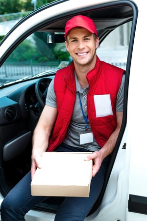 delivers: Colorful picture of courier delivers package. Man is sitting in the car, holding the box and smiling.