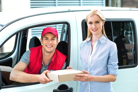 delivers: Colorful picture of courier delivers package for woman. Courier is sitting in the car and smiling. Woman accepts the parcel.