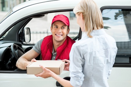 accepts: Colorful picture of courier delivers package for woman. Courier is sitting in the car and smiling. Woman accepts the parcel.