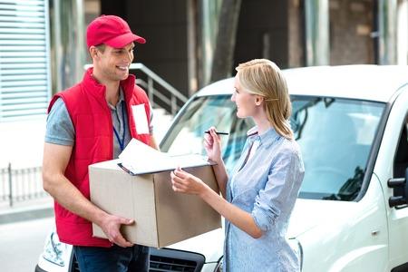 Disegno colorato di corriere consegna pacchetto per donna. Corriere sta dando alla donna una scatola. La donna è la firma del dokument e sorridente. Archivio Fotografico - 44007357