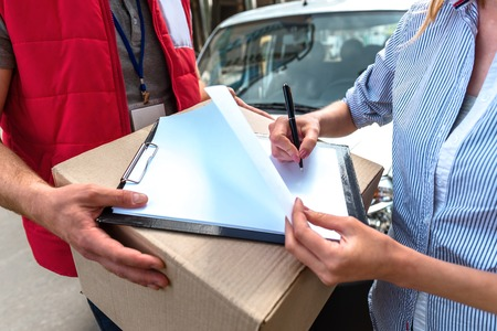 courier man: Colorful picture of courier delivers package for woman. Courier is giving the woman a box. Woman is signing the dokument and smiling.