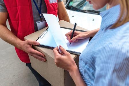 Kleurrijke foto van koerier levert pakket voor vrouw. Courier is geeft de vrouw een doos. Vrouw is de ondertekening van het dokument en glimlachen. Stockfoto