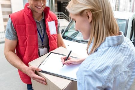 Kleurrijke foto van koerier levert pakket voor vrouw. Courier is geeft de vrouw een doos. Vrouw is de ondertekening van het dokument en glimlachen.