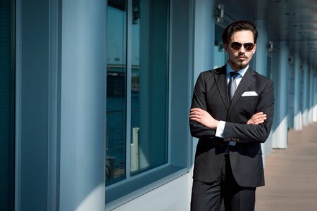 business centre: Photo of handsome young businessman standing near business centre. Man wearing suit and sunglasses, and looking at camera. Stock Photo