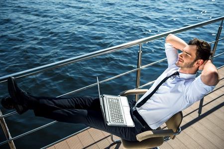 descansando: Foto de la joven y apuesto hombre de negocios sentado y relajante cerca del r�o. El hombre llevaba traje y usando la computadora port�til