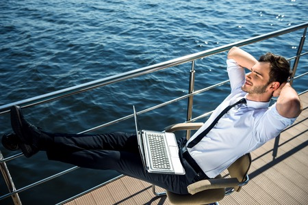 resting: Photo of handsome young businessman sitting and relaxing near river. Man wearing suit and using laptop Stock Photo