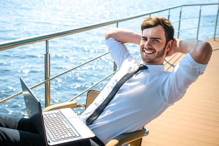 Foto di giovane uomo d'affari seduta e rilassante vicino al fiume. L'uomo che indossa tuta, allegramente sorridente, guardando a porte chiuse e con laptop Archivio Fotografico - 45246169