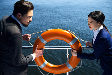 business life: Photo of young business man and woman standing near river. Woman and man wearing suits, seriously looking at each other and holding orange life preserver