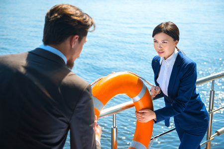 life preserver: Photo of young business man and woman standing near river. They holding orange life preserver. Woman seriously looking at her opponent Stock Photo