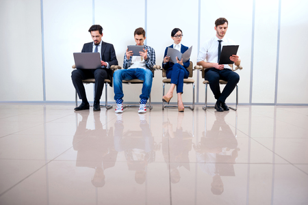 informal clothes: Photo of young creative business team of four with documents and computers. They sitting in a row and working. One man wearing informal clothes