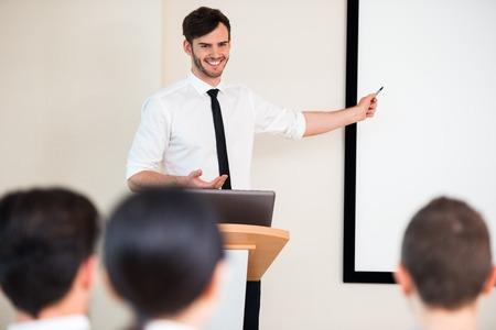 Foto von schönen jungen Geschäftsmann macht Präsentation mit White Seminar oder Meeting Geschäftsleute