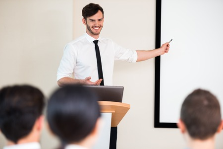 young conference: Photo of handsome young businessman making presentation with whiteboard on seminar or meeting to business people