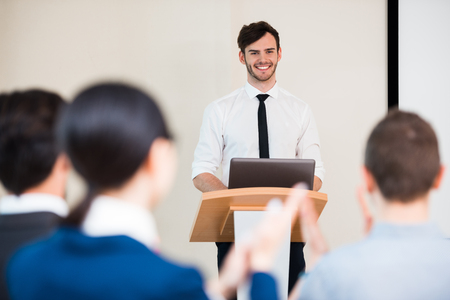 teaching adult: Photo of handsome young businessman making presentation with whiteboard on seminar or meeting to business people