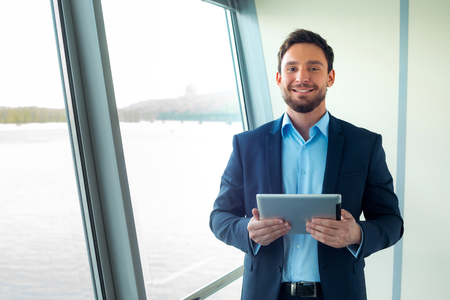 work suit: Portrait of handsome young businessman looking at camera and using tablet computer. Office interior Stock Photo