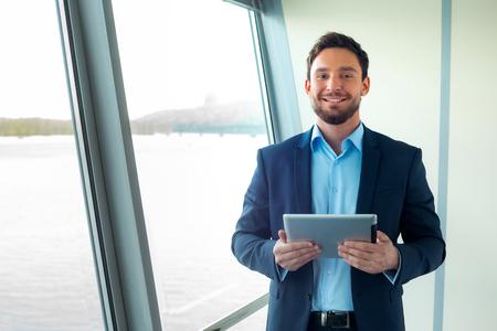 Ritratto di giovane uomo d'affari guardando la fotocamera e utilizzando il computer tablet. interiore dell'ufficio Archivio Fotografico - 45246902