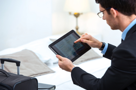 Young businessman using and looking at tablet computer while sitting in cozy hotel room with suitcase