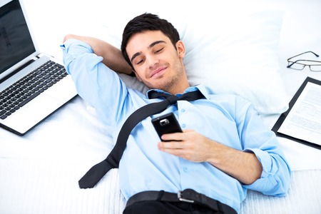 Young smiling businessman lying in cozy hotel room on big white bed with laptop, documents and using phone