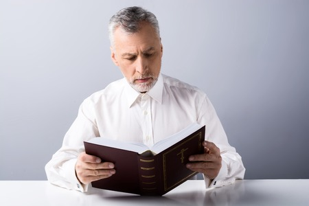 cleric: Photo of old man praying to God and reading Bible