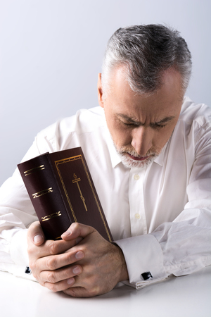 concetrated: Photo of concetrated old man praying to God and holding Bible