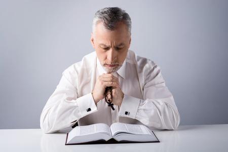 biblia: Foto de un hombre de edad rezando a Dios con el rosario y la lectura de la Biblia