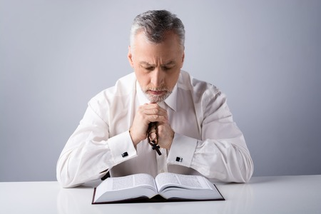cleric: Photo of old man praying to God with rosary and reading Bible Stock Photo