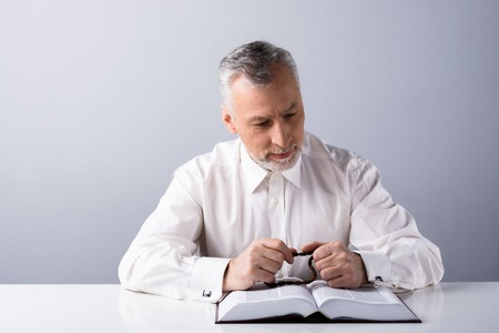 priesthood: Photo of old man praying to God with rosary and reading Bible Stock Photo