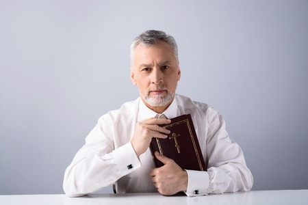 concetrated: Photo of concetrated old man looking at camera and holding Bible