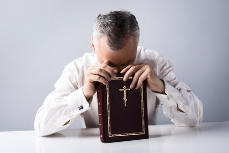 Photo of concetrated old man praying to God and holding Bible