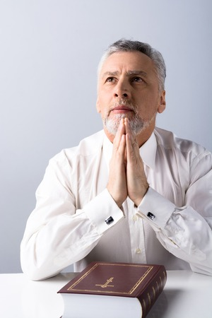 concetrated: Photo of concetrated old man praying to God and looking up with Bible on table Stock Photo