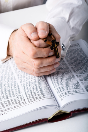 Photo of old man hands with rosary and open Bible
