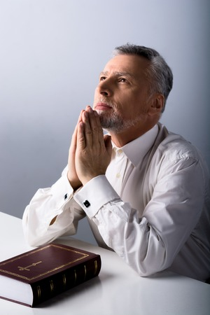 Photo of old man praying to God and looking up with Bible on table