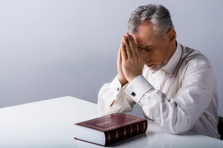 Photo of concetrated old man praying to God with Bible on table Stock Photo