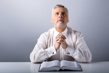 biblia: Foto de un hombre de edad rezando a Dios con la biblia y mirando hacia arriba