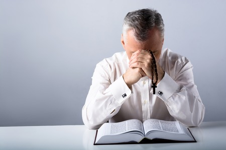 priesthood: Photo of sad old man praying to God with rosary and open Bible
