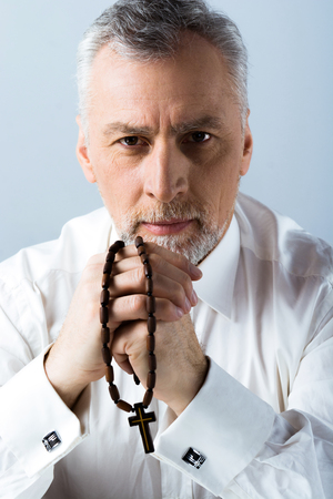 Photo of concetrated old man looking at camera and holding rosary