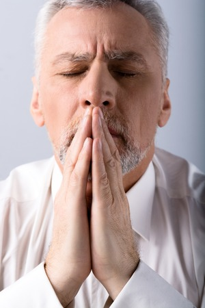 Portrait of concetrated old man praying to God with closed eyes Stock Photo