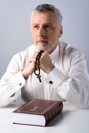 Photo of concetrated old man praying to God with rosary and Bible on table
