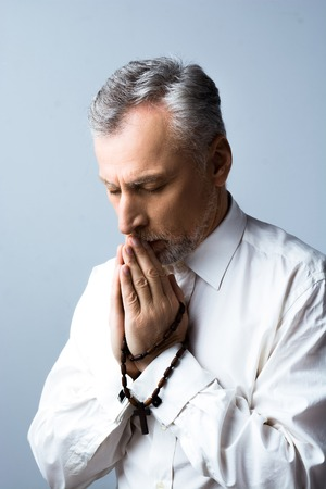 concetrated: Portrait of concetrated old man praying to God with rosary and closed eyes