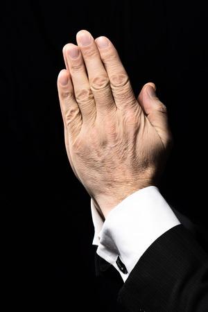 Close up photo de vieilles mains de l'homme en prière à Dieu sur fond noir