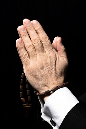 black hands: Close up photo of old man hands praying to God with rosary on black background