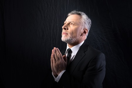 Portrait of concetrated old man praying to God and looking up on black background Stock Photo