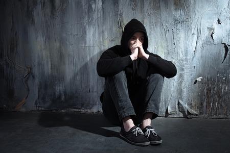 Foto van wanhopige jonge drugsverslaafde dragen kap en zit alleen in het donker