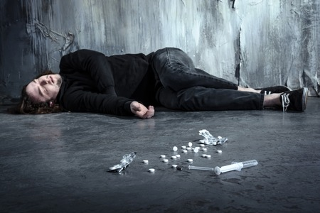 Foto van wanhopige jonge drugsverslaafde lag alleen in het donker na het nemen van heroïne en pillen